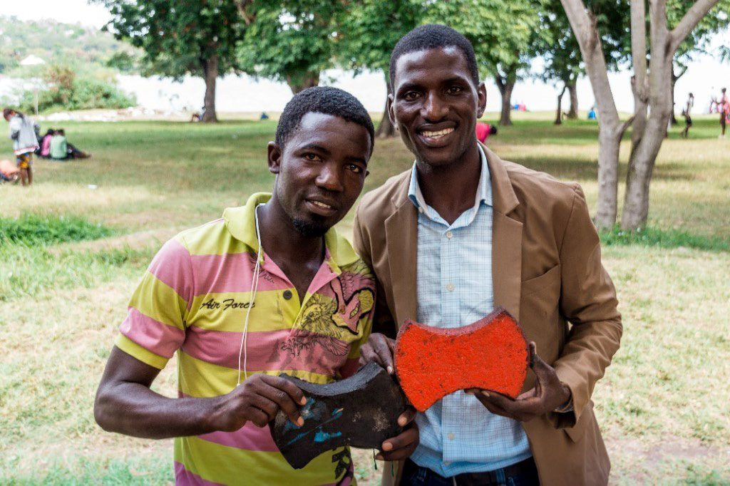 Two men displaying their product, plastic paving blocks, created as a result of the diversity of programming through the EQWIP HUBs project.